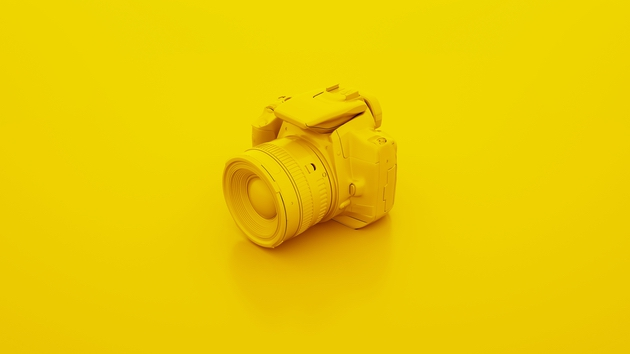 How to use camera settings: Photo of a  DSLR camera on a yellow background.