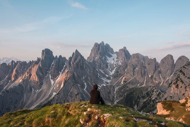 Landscape photo: Mountains and a person sitting on the edge