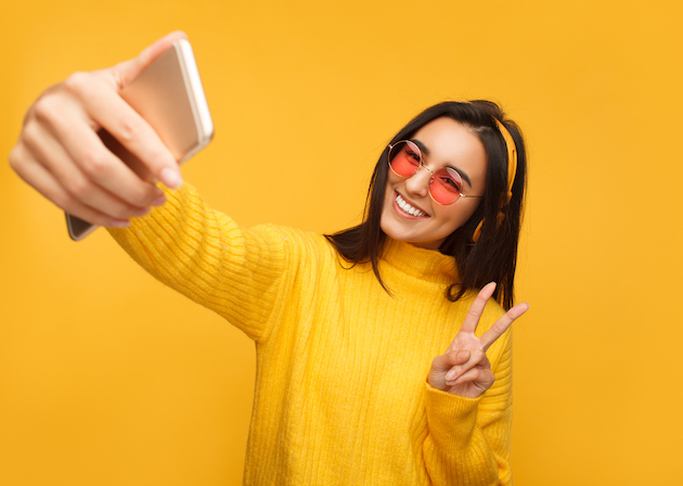 How to take better selfies: A girl taking a selfie with her iPhone on a yellow background